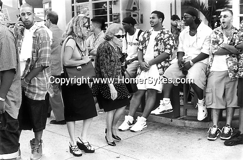 Two stressed looking business women push through a crowd of young men hanging out South Beach Miami Florida USA  1999