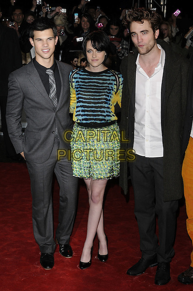 "TAYLOR LAUTNER, KRISTEN STEWART, ROBERT PATTINSON .Attending ""The Twilight Saga: New Moon"" Fan Event at the Battersea Evolution, London, England, UK, November 11th 2009.full length blue and black green striped print top skirt dress pattern yellow white shirt grey gray coat trousers black tie hand in pocket cast mustard orange poppy shoes shoes bare legs .CAP/CAN.©Can Nguyen/Capital Pictures."