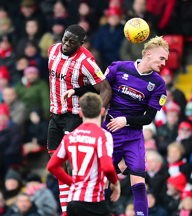 Lincoln City's John Akinde vies for possession with  Grimsby Town's Ludvig Ohman<br /> <br /> Photographer Andrew Vaughan/CameraSport<br /> <br /> The EFL Sky Bet League Two - Lincoln City v Grimsby Town - Saturday 19 January 2019 - Sincil Bank - Lincoln<br /> <br /> World Copyright &copy; 2019 CameraSport. All rights reserved. 43 Linden Ave. Countesthorpe. Leicester. England. LE8 5PG - Tel: +44 (0) 116 277 4147 - admin@camerasport.com - www.camerasport.com