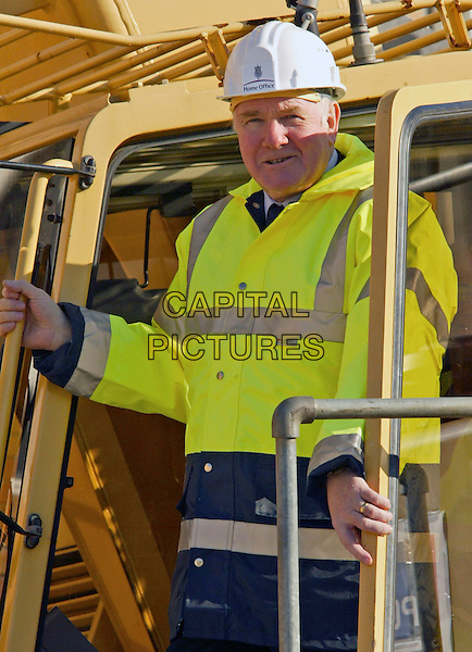 JOHN REID (HOME SECRETARY) .Helps with the building of a new prison block at High Down Prison, UK..November 3rd, 2006.Ref: FEE.half length yellow fluorescent jacket hard hat construction.www.capitalpictures.com.sales@capitalpictures.com.©FEE/Capital Pictures