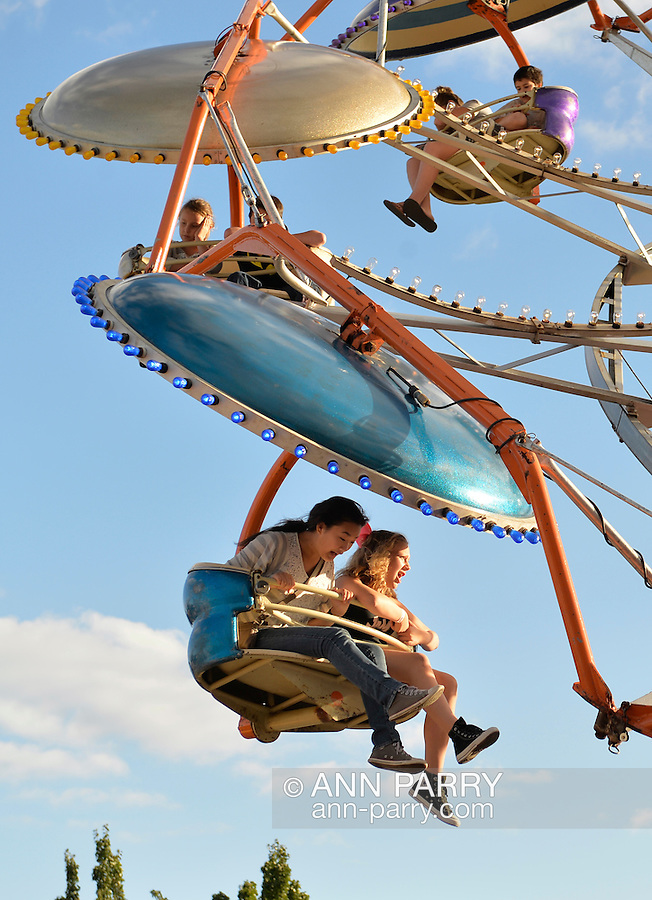 Bellmore, New York, U.S. 22nd September 2013. Two girls scream while riding the Tilt-A-Whirl carnival ride at the 27th Annual Bellmore Festival, featuring family fun with exhibits and attractions in a 25 square block area, with over 120,000 people expected to attend over the weekend.