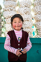 A portrait of a young girl next to her family shop which sells balls made of dried yogurt, a delicacy. Kyrgyzstan.