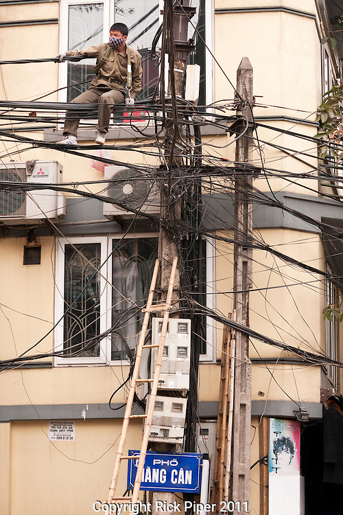 Repairman on power lines at the intersection of Hang Buom St and Hang Can St Hanoi Old Quarter, Vietnam