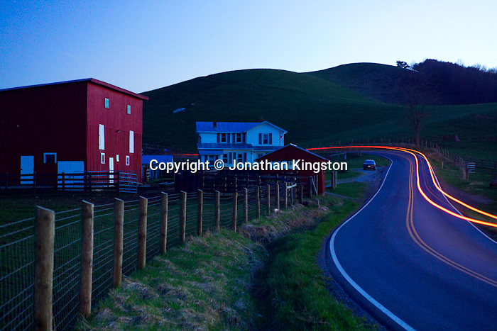 FLOYD, VA,  A car's taillights illuminate the road near a farm in Pleasant Valley, Floyd, Virginia.