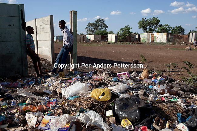 KHUTSONG, SOUTH AFRICA - OCTOBER 16: Bafana Mashata, age 17, talks to a friend next to uncollected garbage on October 16, 2012, in Khutsong, South Africa. Khutsong, a black township. is located about 56 miles west of Johannesburg, and surrounded by gold mines. Because of recent strikes many mineworkers has been fired which is making the poverty worse here. The communal toilets are dirty and often broken. (Photo by Per-Anders Pettersson)