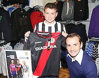 Jamie McAvoy the first customer to get the new top St Mirren manager Danny Lennon along with Marc McAusland, Jim Goodwin and Sam Parkin celebrating the launch of the new black away kit, featuring a diagonal red stripe across the shirt at JD Sports, Paisley on 12.9.12.