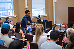 Cecille Labuda, associate professor of physics and astronomy, hands out the final exam in her physics class. Photo by Kevin Bain/University Communications Photography.