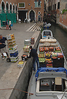 Unloading crates and boxes of fruit from cargo barge, at the Rialto market. Venice, Italy, May 2007.
