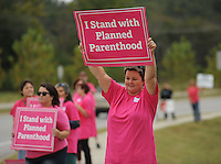 NWA Democrat-Gazette/ANDY SHUPE<br /> Leah Childress of Fayetteville holds a sign Wednesday, Sept. 30, 2015, in support of Planned Parenthood during a rally along Crossover Road in Fayetteville. The rally was organized by members of the Omni Center for Peace, Justice and Ecology's EcoFeminist Study and Action Group as a part of a national rally in support of Planned Parenthood's Pink Out day, which was Tuesday.