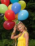 Young happy woman with a bunch of colorful air balloons