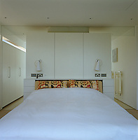 An open-ended partition wall, which doubles as a headboard, separates the master bedroom from the ensuite bathroom