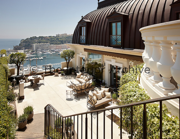 Metal furniture is arranged on an outside terrace area of a luxury penthouse apartment, which overlooks Monte Carlo harbour.