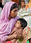 A Rohingya woman, having just crossed the border from Myanmar, comforts her child as she waits to complete registration in the Kutupalong Refugee Camp near Cox's Bazar, Bangladesh. More than 600,000 Rohingya refugees have fled government-sanctioned violence in Myanmar for safety in this and other camps in Bangladesh.