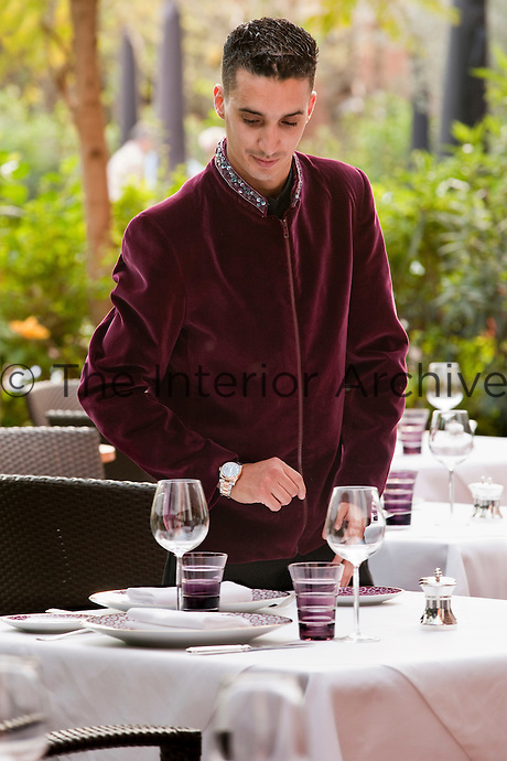 A waiter applying the last touches to the laid tables in the dining room