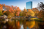 The John Hancock tower by I. M. Pei stands above fall foliage along the Charles River Esplanade, Boston, MA, USA