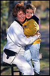 portrait of mother embracing young son in park