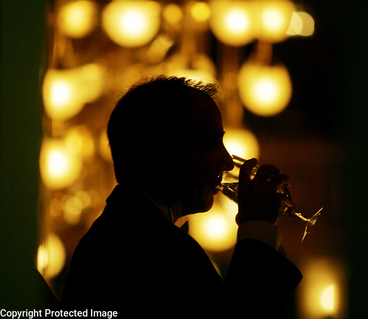 Silhouetted by a chandelier, Rick Scarola takes a sip of water while dining on the balcony overlooking the main floor during the 2006 Symphony Ball benefiting the Nashville Symphony at the Schermerhorn Symphony Center in Nashville, Tenn.,  Saturday, Dec. 9, 2006.-&amp;#xD;Jeff Adkins /for The Tennessean<br />