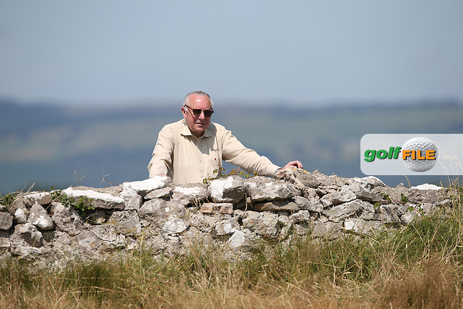 Specator on the dry stone wall enjoying the action on the 6th during Round One of the 2014 Senior Open Championship presented by Rolex from Royal Porthcawl Golf Club, Porthcawl, Wales. Picture:  David Lloyd / www.golffile.ie
