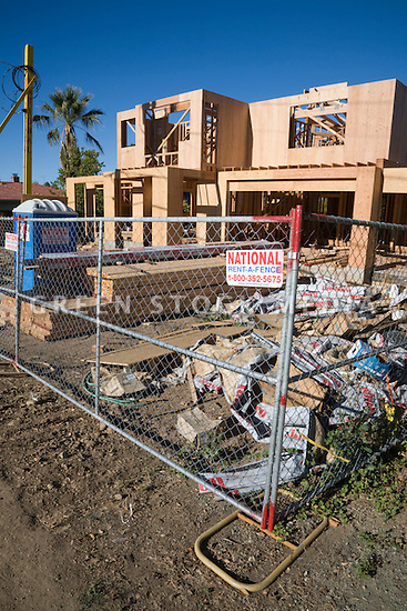 A metal chain link fence cordons off a large single family wood frame home construction site.