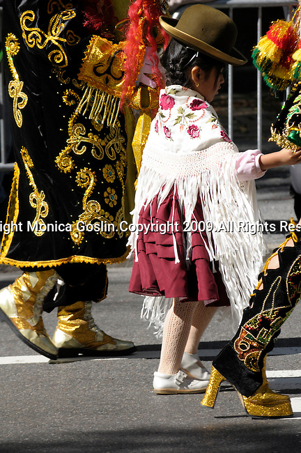 The Hispanic Parade in New York City. A girl wearing traditional clothes walks between two women, all representing Bolivia in the Hispanic Parade in New York City.