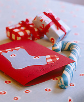 Detail of a Christmas card made with a cut out fabric stocking next to a stick of rock candy and miniature gifts