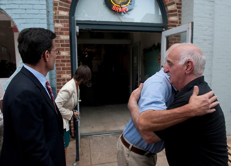 UNITED STATES - August 24 : Eric Cantor, R-VA., peeks inside Bella-Mia's Italian American Deli that has been condemned from damage sustained from yesterdays earthquake. Mayor of Culpeper Virginia Chip Coleman hugs the owner Carmine (would not give last name) and promises him that the beloved deli will reopen. The damage from the earthquake in downtown Culpeper was substantial and lots of streets and businesses are closed. (Photo By Douglas Graham/Roll Call)