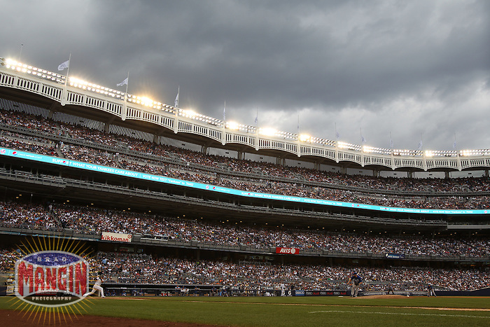 NEW YORK, NY - JULY 25:  Nick Swisher #33 of the New York Yankees bats against the Kansas City Royals as storm clouds gather overhead during the game at Yankee Stadium on July 25, 2010 at Yankee Stadium in the Bronx borough of New York City. Photo by Brad Mangin