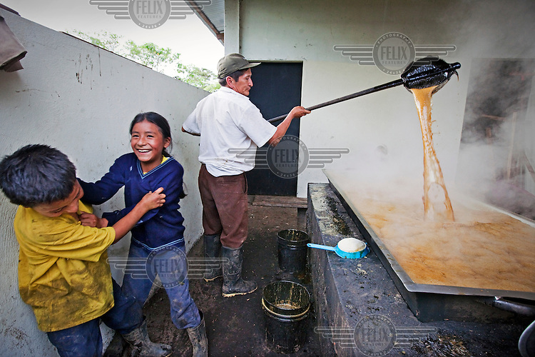 Children play as their father boils sugar cane to make rum at a distillery in an indigenous village in the rainforest.