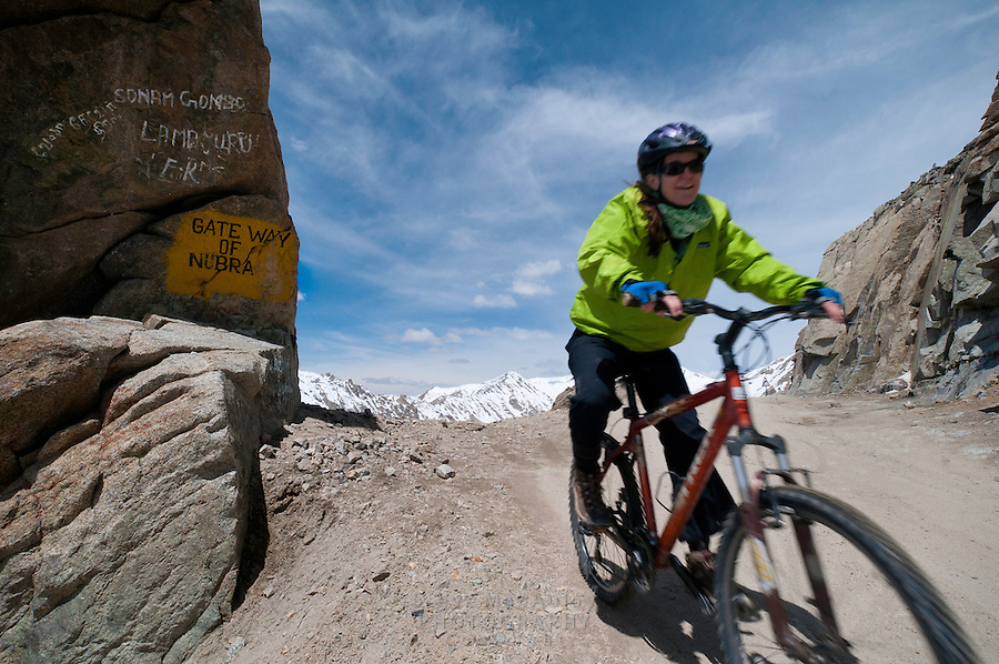 """Mountain biking past the """"Gateway of Nubra"""", on the highest motorable road in the world,  Himalayan Mountains, Ladakh, India."""