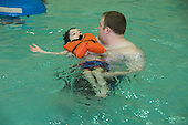 MR / Albany, NY.Langan School at Center for Disability Services .Ungraded private school which serves individuals with multiple disabilities.Teaching assistant holds non ambulatory student wearing life jacket in the pool. Students in this class swim once a week as part of their physical education program. Boy: 8, cerebral palsy, spastic quadriplegic, nonverbal with expressive and receptive language delays.MR: Hac2; Gar7.© Ellen B. Senisi