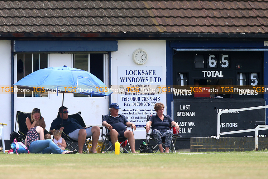 Spectators sit near the scoreboard during Upminster CC vs Hornchurch CC, Shepherd Neame Essex League Cricket at Upminster Park on 8th July 2017