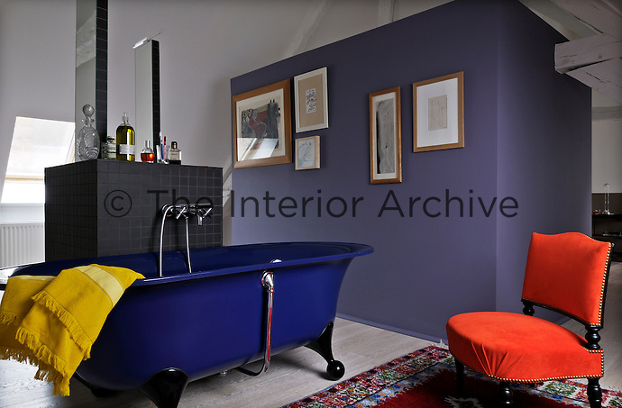 A lavender colour partition wall in the master bedroom conceals a surprising dark blue bath tub
