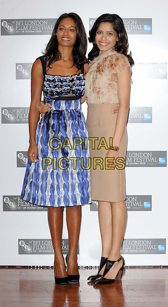 RULA JEBREAL (SCREENWRITER) & FREIDA PINTO  .The 'Miral' press conference & photocall, London Film Festival, Vue West End, Leicester Square, London, England..October 18th, 2010.full length blue silver grey gray ruffle print dress beige skirt top blouse silk satin floral print arm around waist ankle shoes .CAP/WIZ.© Wizard/Capital Pictures.