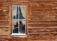 Old ragged curtains hang in window on Tom Miller House, Bodie State Historic Park, California, USA