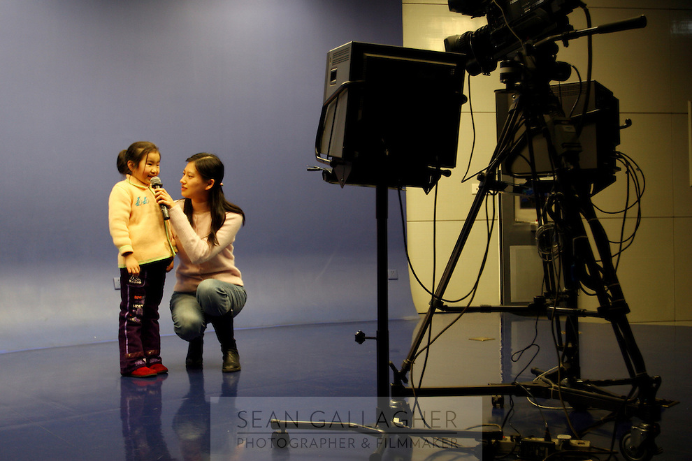 CHINA. Shanghai. A young girl and woman in a mock TV  studio in the Shanghai Science and Technology Museum (?????; pinyin: Shàngh?i ke¯jì gu?n) is a large museum in Pudong, Shanghai, close to Century Park, the largest park of the city. The construction of the museum cost 1,75 billion RMB, and the floor area is 98 000m2 .2008..