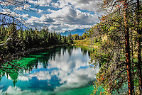 Vibrant photo of lake with reflections of clouds and sky in the water. One of the five lakes on the Five Lakes Trail in Jasper National Park.