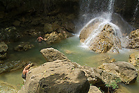 Man and woman climbing rocks and swimming at the foot of a waterfall, Soroa Cascade, Cuba.