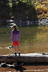 Girl standing on log, watching Mallard ducks at Bear Lake in Rocky Mountain National Park, Estes Park, Colorado. .  John offers private photo tours in Denver, Boulder and throughout Colorado. Year-round Colorado photo tours.