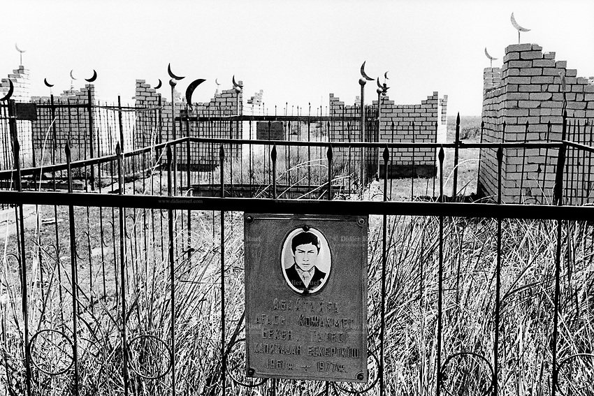 Kazakhstan. Sarzhal. Muslim graveyard with half-moon signs from the time of  former Soviet Union. The village of Sarzhal is near the Semipalatinsk Polygon ( called today National Nuclear Center of Kazakhstan). The deceased man (commit suicide) is a third generation victim of the 456 atomic testing - 116 atmospheric, 340 underground - from 1949 to 1989. The regions high frequency of deaths is primarily due to fallout from nearby nuclear test sites. The dead man shows the human and environmental effects of nuclear radiation, genetic contamination and pollution from atomic tests programs of the former Soviet Union. Sarzhal is located in the Eastern Kazakhstan Province. © 2008 Didier Ruef