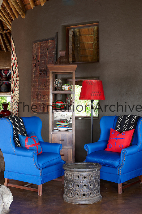 Two blue armchairs and a floor lamp with a red shade in a sitting area at the Singita Pamushana Lodge, Malilongwe Trust, Zimbabwe