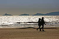 Pictured: A couple walk on the beach overlooking Mumbles at Swansea seafront in Wales, UK. Friday 23 February 2018<br /> Re: Parts of the UK have been enjoying sunshine with freezing cold temperatures.