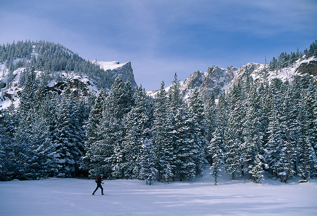 Man snowshoeing on new snow beneath Hallett Peak, Rocky Mtn Nat'l Park, CO