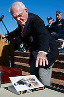 Saturday, November 8, 2008, Mt. Soledad Veterans Memorial La Jolla California.   Ed Ward, 1st Vice President, Mt. Soledad Memorial Association, reaches for a copy of Jimmy Stewart's biography, Bomber Pilot, while addressing the crowd attending a ceremony on Mount Soledad.  Brigadier General James Maitland Stewart, United States Air Force, a highly decorated WWII pilot was honored with a special plaque during at a dedication ceremony attended by his daughter and other family members.  Stewart, who would have been 100 years old this year was better known to most of the world as a highly acclaimed Hollywood actor.