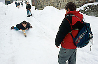 Bosnia and Herzegowina. Republika Serpska. Srebrenica. Young boys, on the way back from school, play in the snow during the winter season. A boy slides down the hill, lying down on a mono ski. © 2005 Didier Ruef