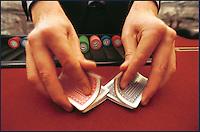 le mani del croupier mischiano le carte da gioco. Black jack,