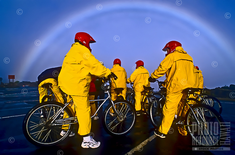 After sunrise on a rainy morning and framed by a rainbow, a group of bicyclists gets ready to start their ride at 9,745 feet in Haleakala National Park, Maui.