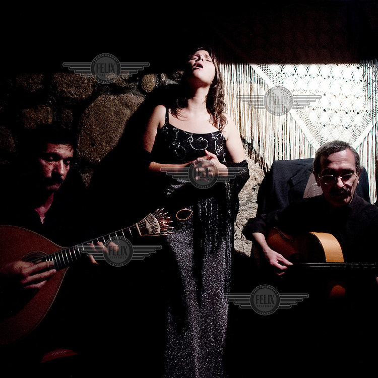 A woman sings accompanied by guitarists at a restaurant.