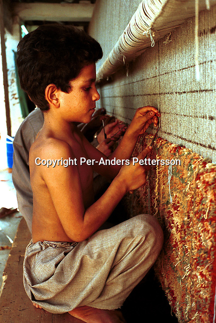 disichl00015 Social Issues Child labour. Kameen age 5, an Afghan refugee boy works as a carpet weaver of Afghan carpets in an illegal factory on October 1, 2001 in Attock, Pakistan. This village has about 20 carpet factories, where children aged from 5 years old work usually from 4 am to 11 pm in bad conditions and for low wages. This is one of the few chances for Afghan refugees in the village to make money. The children are often beaten and denied school studies. .©Per-Anders Pettersson/ iAfrika Photos..