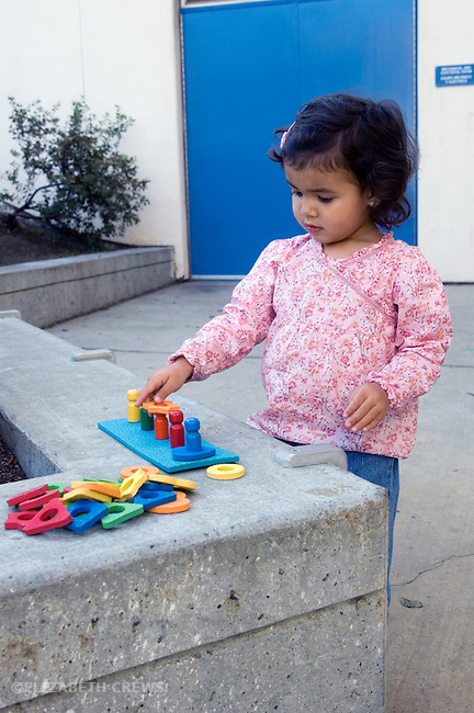 Berkeley CA Girl, two and a half, half Nepalese, practicing shape and color sorting with educational toy  MR