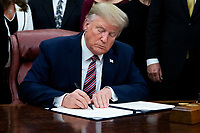 US President Donald J. Trump signs 'H.R. 724, the Preventing Animal Cruelty and Torture Act', in the Oval Office of the White House in Washington, DC, USA, 25 November 2019.<br /> Credit: Michael Reynolds / Pool via CNP/AdMedia